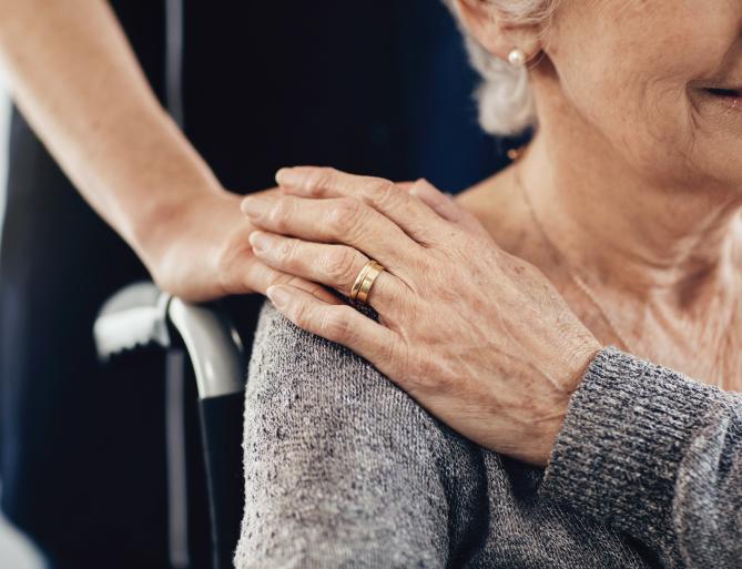 hand on senior womans shoulder