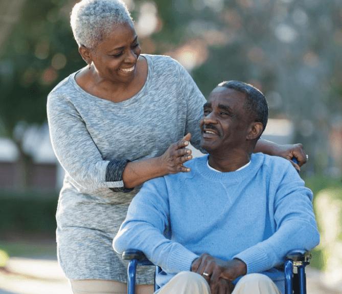 woman pushing senior man in his wheelchair